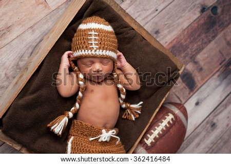A two week old newborn baby boy sleeping in wooden crate and wearing a crocheted American football costume. - stock photo