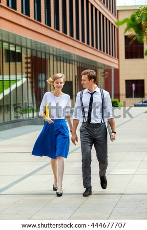 A two young business-people are walking along office building