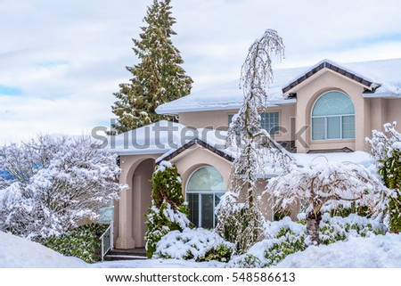 A typical american house in winter. Snow covered.