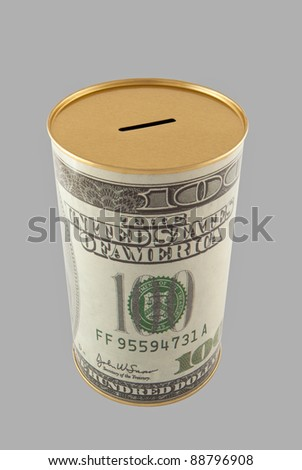 A typical coin bank depicting the print of a 100 dollar bank note on its cylindrical surface, isolated over a grey background. Includes clipping path. - stock photo