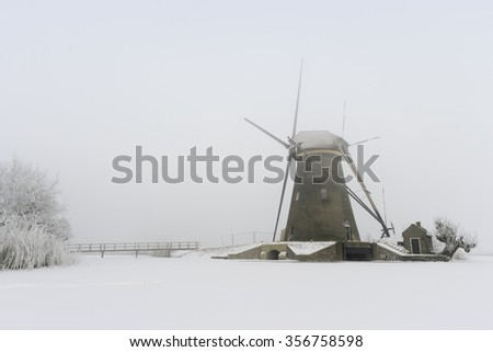 A typical Dutch scenery: Windmill at the Kinderdijk in The Netherlands during winter. - stock photo