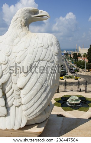 A typical eagle statue in the Bahai gardens, on the slopes of the Carmel Mountain, in Haifa, Israel. The German colony is in the background - stock photo