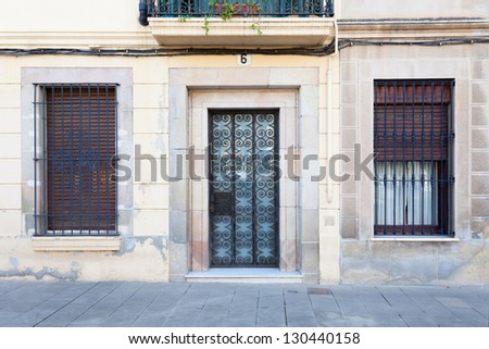 A typical facade of the Sarri�  quarter of Barcelona, Spain (one door, two windows). In this area, ground level homes abound and many doors and windows preserve the same look they had some decades ago. - stock photo