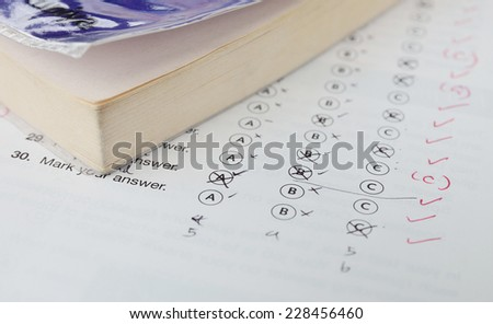 A typical multiple choice answer sheet and textbook. - stock photo