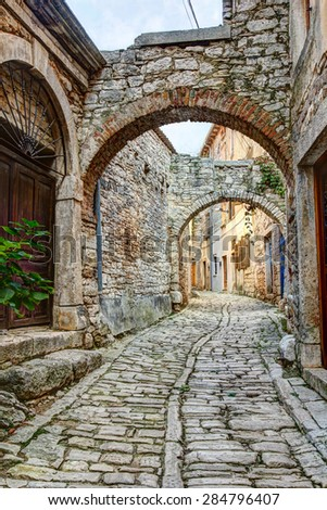 A typical narrow street or alley with stone houses in the hilltop town of Bale or Valle in Istria, Croatia.