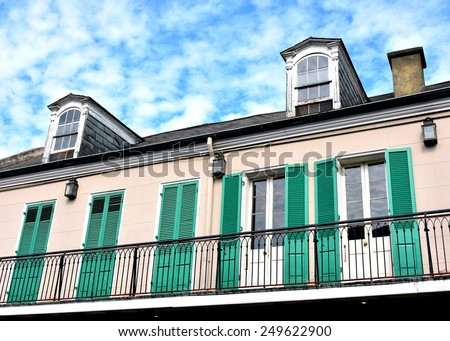 A typical New Orleans French Quarter style balcony with green shutters and dormers. - stock photo