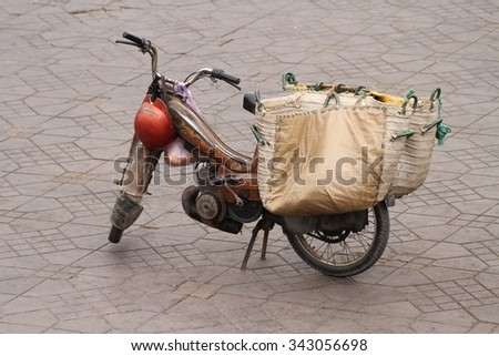A typical old motor bike with carry bags in Jemaa el Fnaa Square, Marrakesh, Morocco. - stock photo