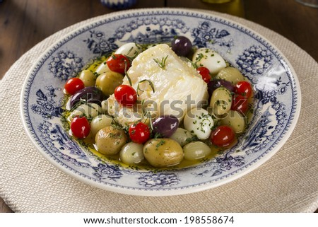 A typical Portuguese dish with codfish called Bacalhau do Porto in a original portuguese plate. - stock photo