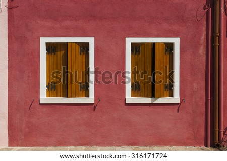 A typical red wall of an house of Burano, a small island of the venetian lagoon. Italy. Taken on August 21, 2015 - stock photo