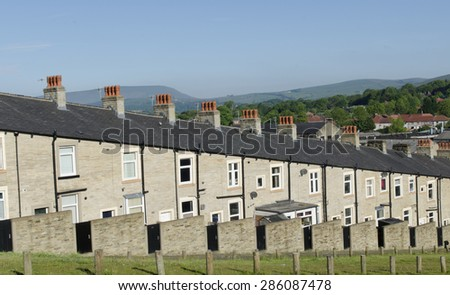 A typical row of Lancashire town stone facade built and slate roof covered terraced houses. Red chimney stacks top the buildings with the hills visible in the distance - Taken early morning. - stock photo