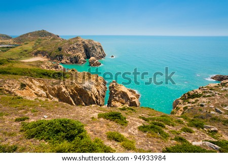 A typical set of dramatic rocky high cliffs line the edge of azur, turquoise blue ocean water of Juguang coastline on the Matsu Islands in Taiwan. Horizontal copy space - stock photo