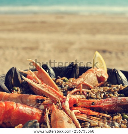 a typical spanish paella with seafood in a paellera, the paella pan, on the beach, with a retro effect - stock photo