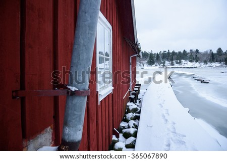 A typical Swedish boathouse is seen along a harbor in the Stockholm Archipelago in Sweden - stock photo