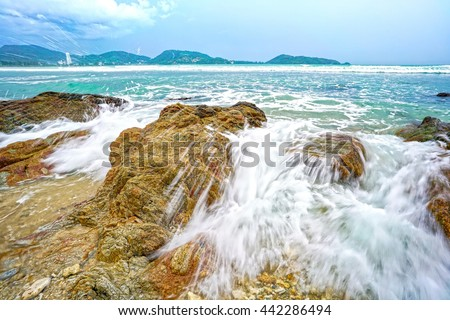 A typical wave splashing on rock seascape photo, taken at an island in the Andaman Sea during monsoon season - stock photo