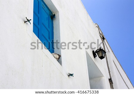 A typical white house in Mykonos in Greece with a dove on the window and blue sky on the background - stock photo