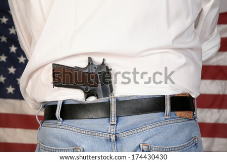 A under cover police officer or concerned citizen has a .45 caliber Pistol Concealed in his back waistband as he stands in front of the American Flag. The perfect image for your 2nd amendment rights - stock photo