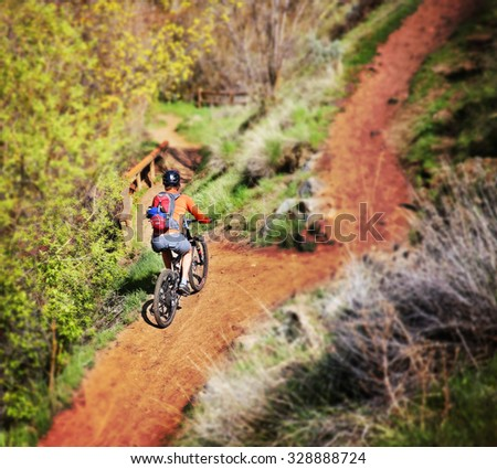 a unique perspective of a person riding a mountain bike up a dirt road toned with a retro vintage instagram filter effect app or action - stock photo