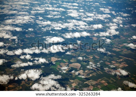 A unique view of Florida USA as seen from high above the clouds, through the window of a Jet Airplane. Florida is known for Alligators, Swamps, Sandy Beaches and is an international vacation spot - stock photo