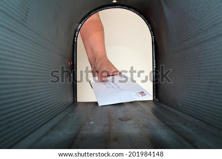A Unique view of someone getting or placing mail in a mail box, shot from the Inside Out.  - stock photo