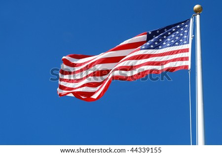 A United States flag against blue sky