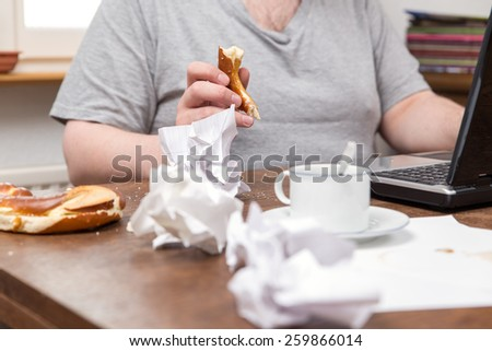 a untidy desk and a thick man with food in his hands - stock photo