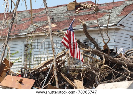 A US American flag rises above a home ruined by a deadly EF-5 tornado. - stock photo