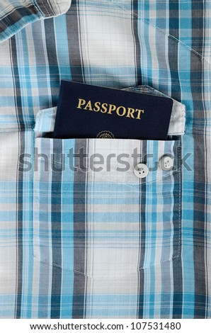 a us passport in a front pocket of plaid shirt - stock photo