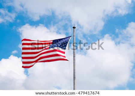 A USA,American or A United States of america flag flies in a strong wind against blue sky