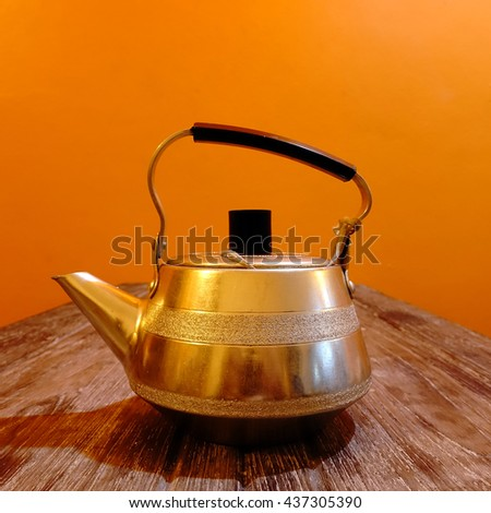 a used aluminum teapot on the wooden table. under the incandescent lamp light in orange tea room. - stock photo