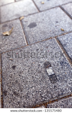 A used dirty band-aid stuck to the pavement. - stock photo