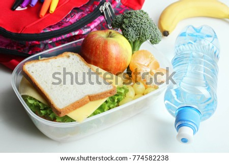 A useful school lunch and a bottle of water on a neutral background.