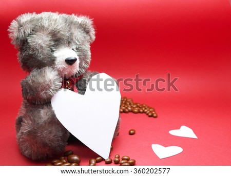 A valentine prop, black teddy bear , chocolates on floor, and three white hearts. Red tone background. Space for texts.