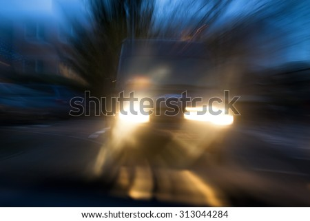 A van approaching in a menacing way in twilight, with deliberate camera shake for the concept of car accident risks - stock photo