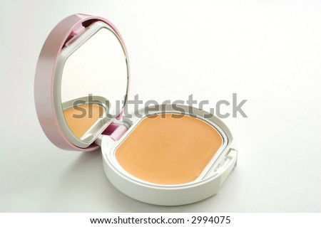 A vanity case of facepowder over white background