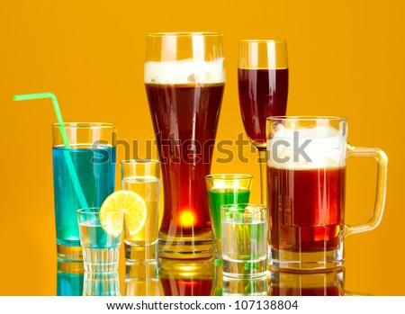 a variety of alcoholic drinks on yellow background - stock photo