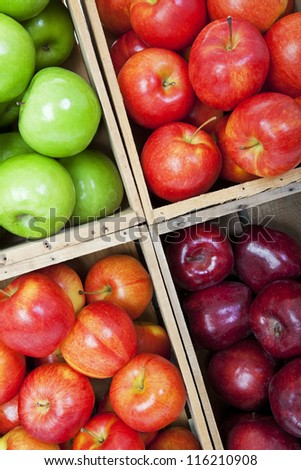 A variety of apples in a market, sorted in wooden bins. - stock photo