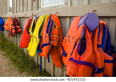 A variety of colorful life jackets hanging on the boathouse wall.