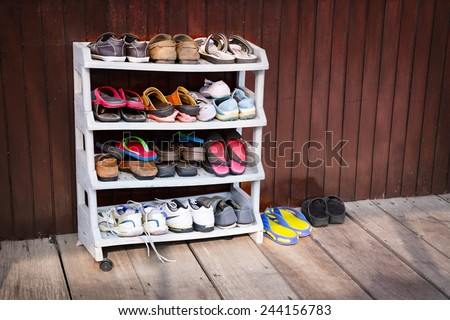 a variety of colorful shoes neatly ordered on a plastic shoe rack outside a wooden