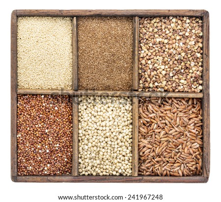 a variety of gluten free grains (buckwheat, amaranth, brown rice, millet, sorghum, teff,  red quinoa) in a rustic wooden box isolated on white - stock photo