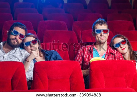 A variety of human emotions of friends holding a cola and popcorn in the cinema.