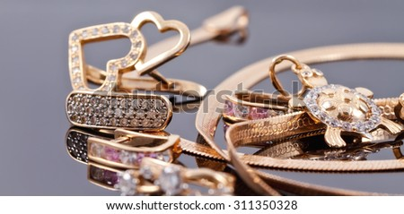 A variety of jewelry on the reflecting surface: the earrings of different styles, chains, rings and a pendant in the shape of turtles - stock photo