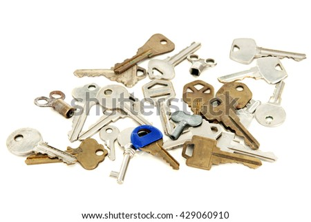 A variety of old gold and silver colored keys on a white background. - stock photo