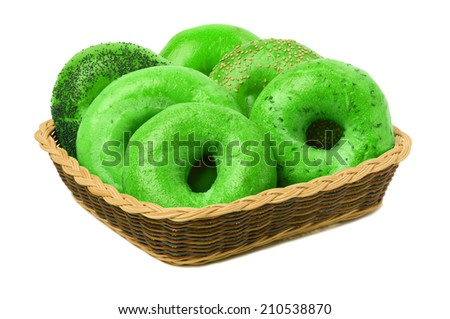 A variety of six green bagels in a basket, isolated against a white background - stock photo