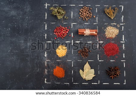 A variety of spices and condiments on a dark background. Anise stars, cinnamon, cloves, bay leaf, basil and other spices - stock photo