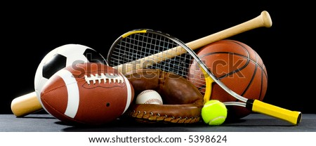 A variety of sports equipment on a black background including an american football, a soccer ball, a baseball, a baseball bat, a tennis racket, a tennis ball, and a basketball - stock photo