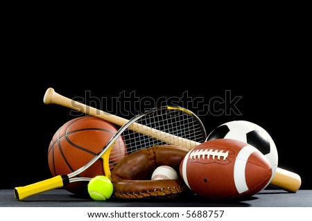A variety of sports equipment on a black background including an american football, a soccer ball, a baseball, a baseball bat, a tennis raquet, a tennis ball, and a basketball - stock photo