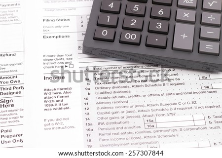 A variety of 2014 United States tax forms with a ballpoint and calculator - stock photo