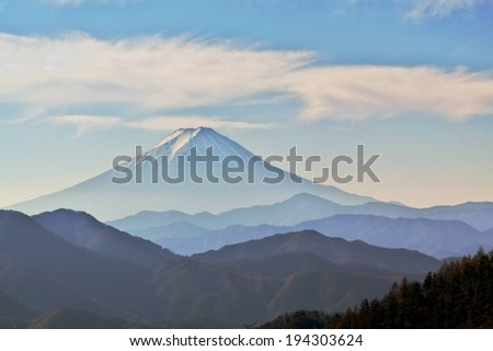 A various amount of hills with a large snow capped mountain in the distance. - stock photo