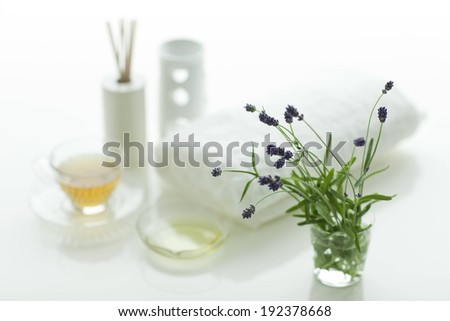 A vase with small purple flowers sits next to a towel and other various objects. - stock photo