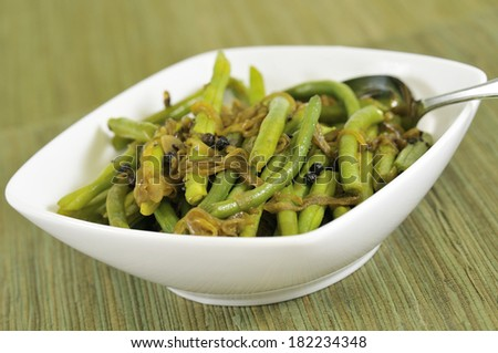 A vegetable dish consisting of green beans, onions, and curry spices, shot at a slighlly angled down direction